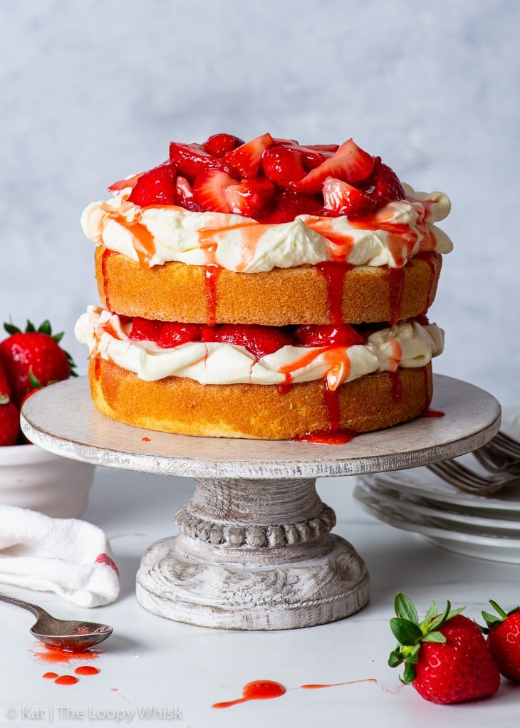 Gluten free strawberry shortcake cake on a wooden cake stand, with a tea towel and dessert plates next to it.