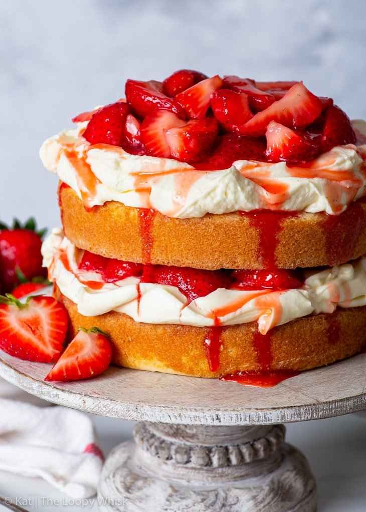 Gluten free strawberry shortcake cake on a wooden cake stand, with more strawberries in the background.