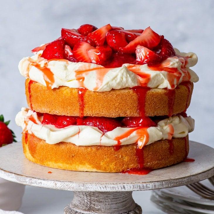 Gluten free strawberry shortcake cake on a wooden cake stand.