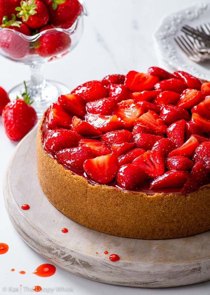 Strawberry cheesecake on a round wooden board.