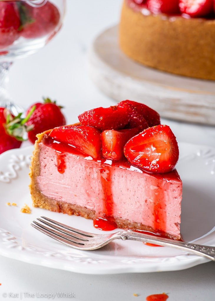 A slice of strawberry cheesecake on a white dessert plate.