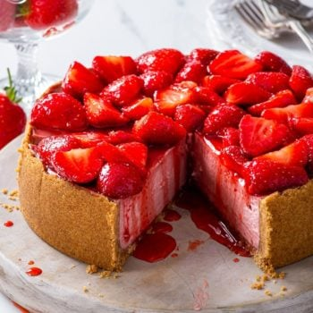 Strawberry cheesecake on a round wooden board with a few slices already cut.