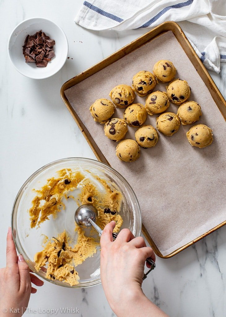 Scooping out individual portions of chocolate chip cookie dough.