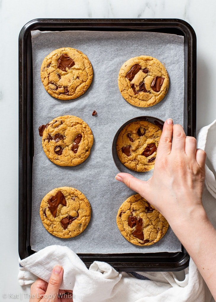 Correcting the shape of chocolate chip cookies with a round cookie cutter.