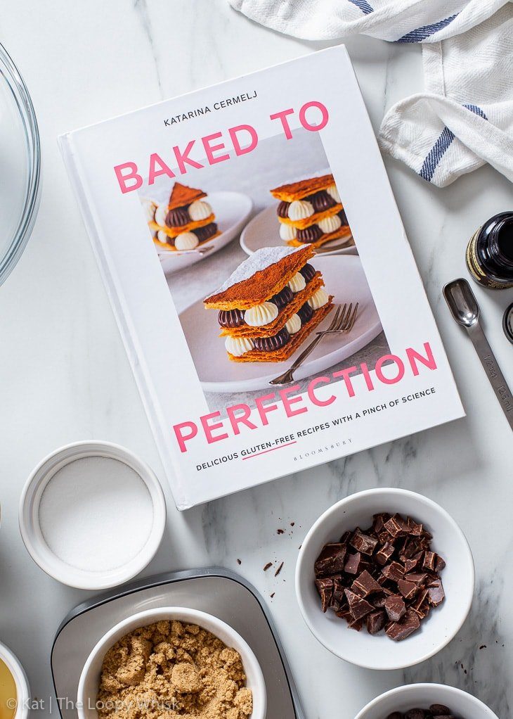 Chocolate chip cookie ingredients and my gluten free baking cookbook Baked to Perfection on a white marble surface.