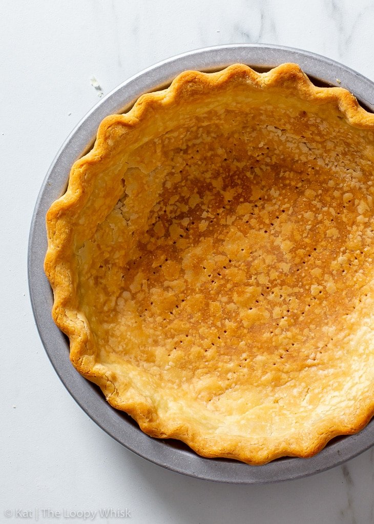 Overhead view of the baked gluten free pie crust in a metal pie dish.