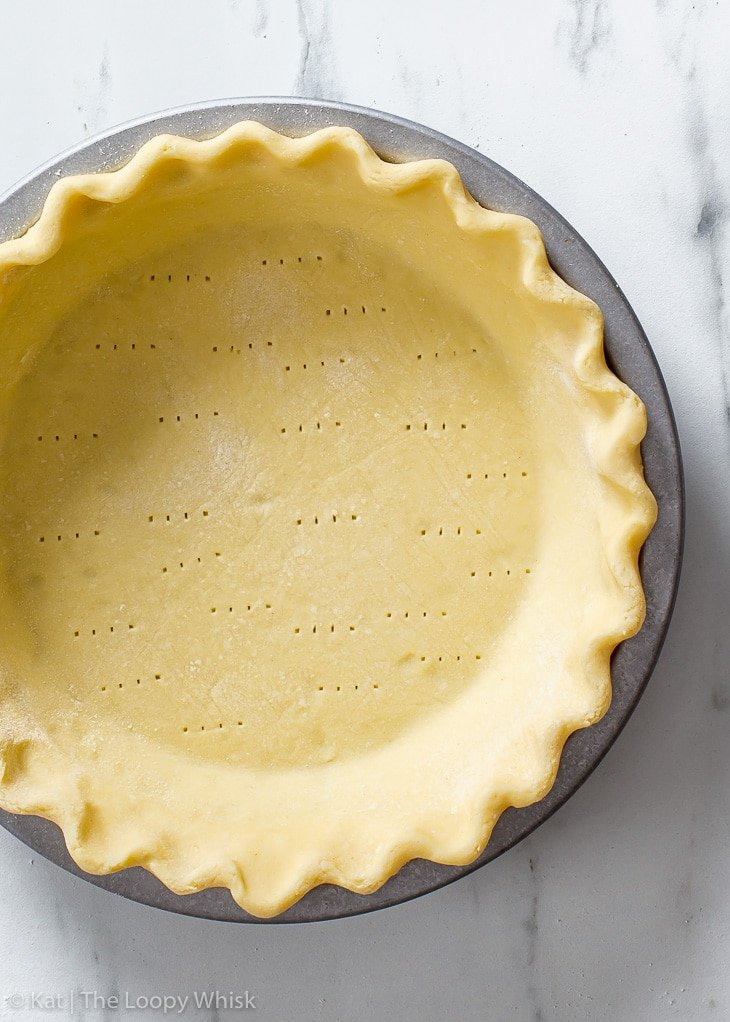 Overhead view of the gluten free pie crust in a metal pie dish before baking.