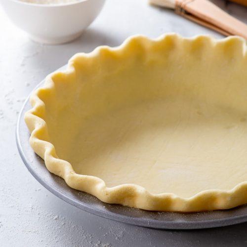 Gluten free pie crust in a metal pie dish before baking.