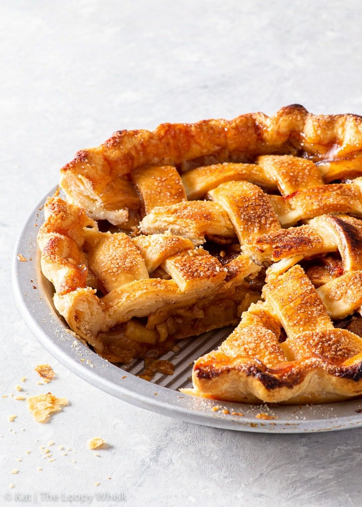 Gluten free apple pie with a few pieces already cut.
