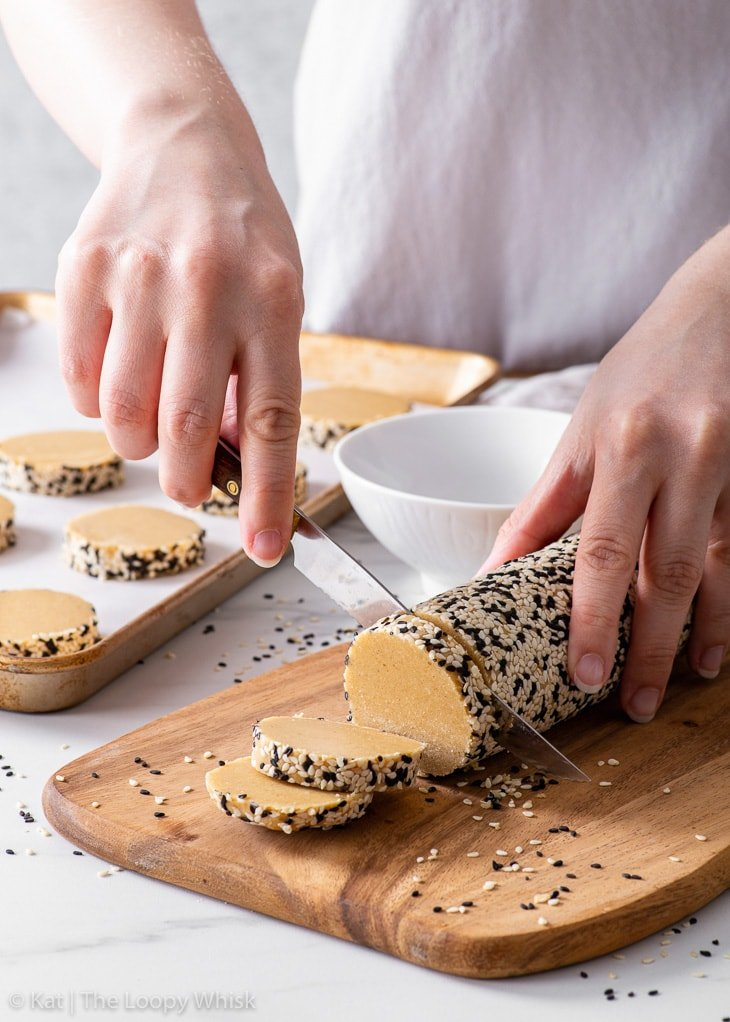 Slicing the cookie dough log into individual cookies before baking.