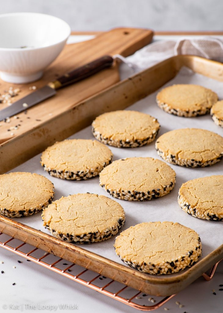 Tahini shortbread cookies on a lined baking sheet after baking.
