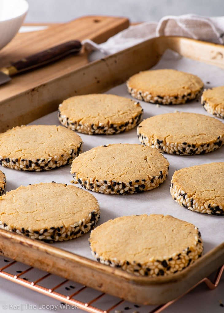 Tahini shortbread cookies on a lined baking sheet.