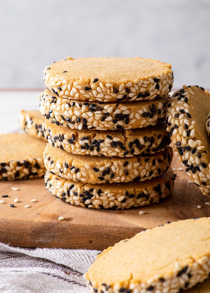 A stack of gluten free tahini shortbread cookies on a wooden board.