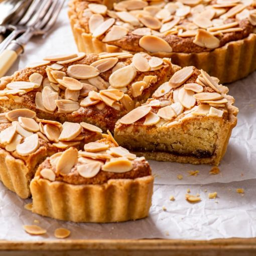 Vegan Bakewell tarts on a baking tray lined with parchment paper.
