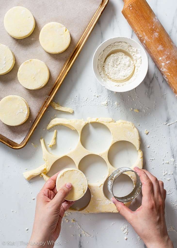 Cutting out gluten free biscuits with a round cookie cutter.