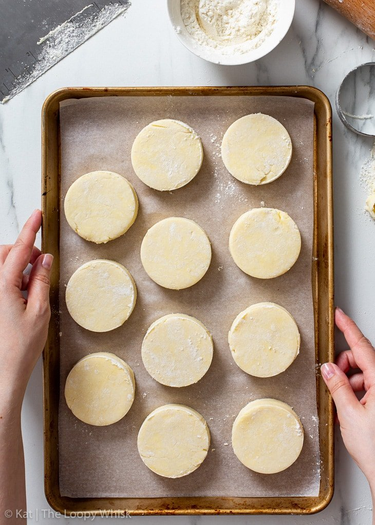 Gluten free biscuits on a lined baking sheet ready for freezing.