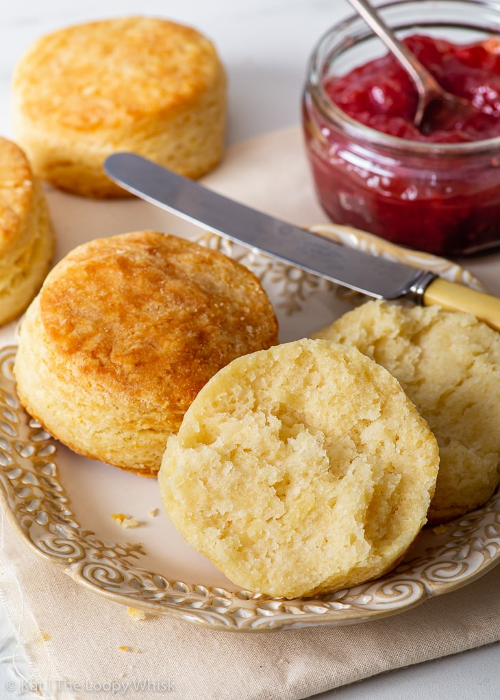 Gluten free biscuits on a small serving plate, one is torn in half.