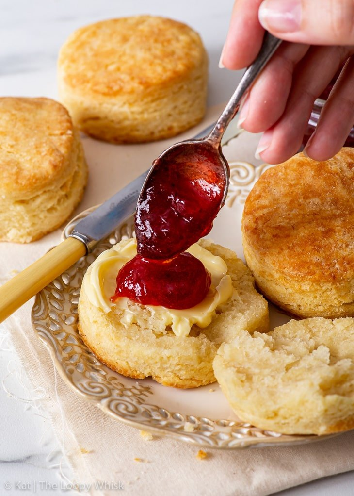 Spooning strawberry jam onto a biscuit.