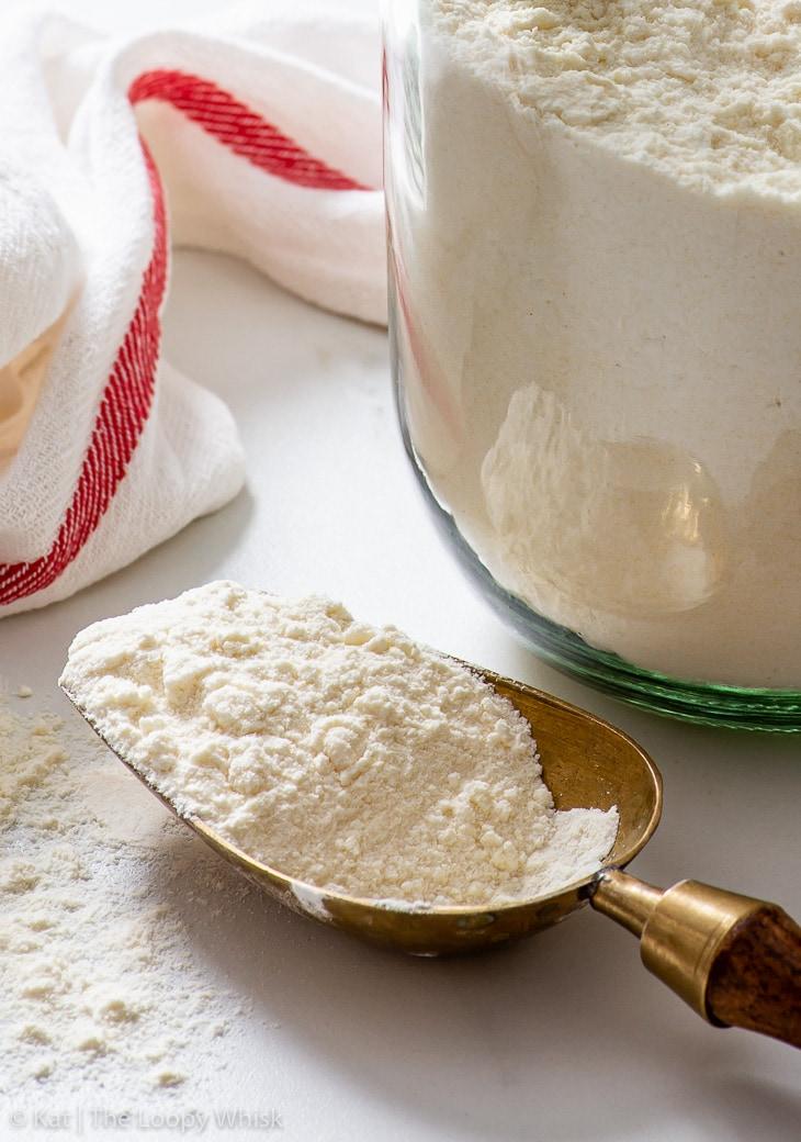 Homemade gluten free flour blend in a brass scoop.