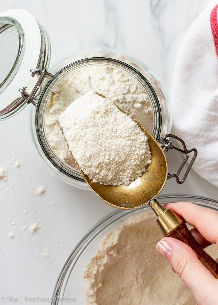 Scooping homemade gluten free flour blend into a glass jar.