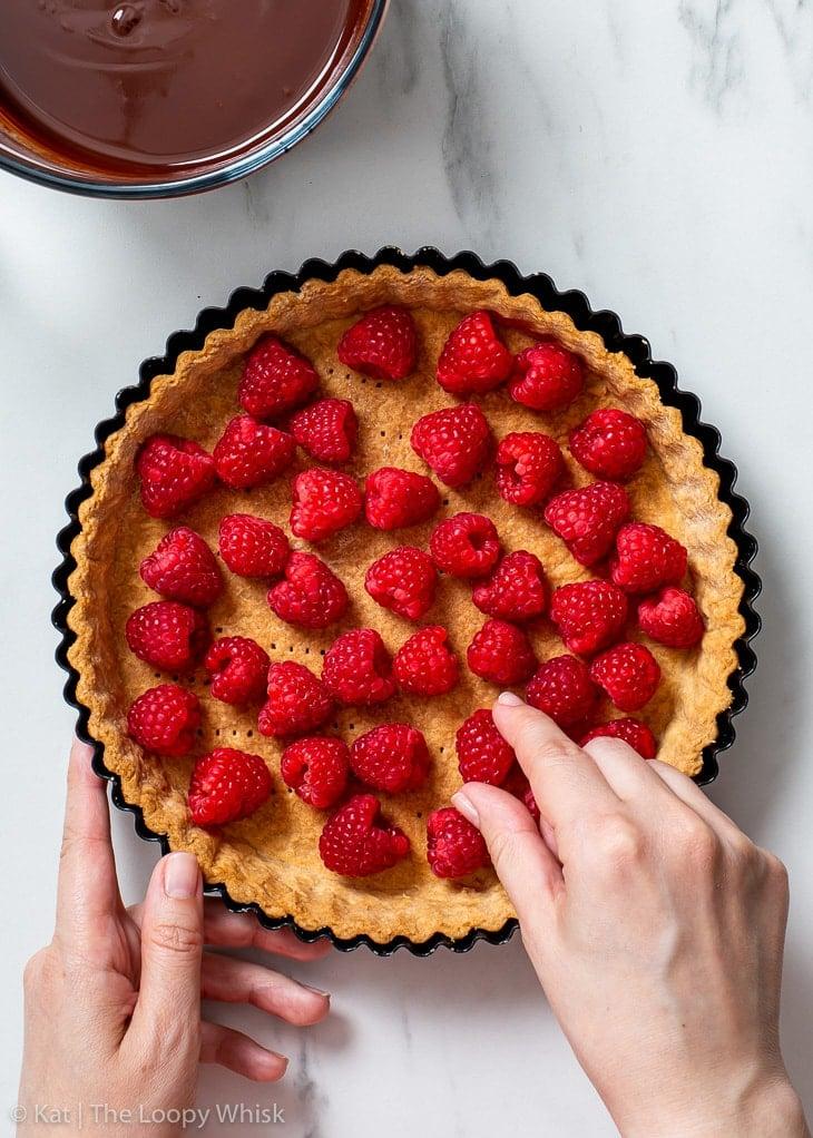 Arranging the fresh raspberries in the blind baked vegan tart shell.