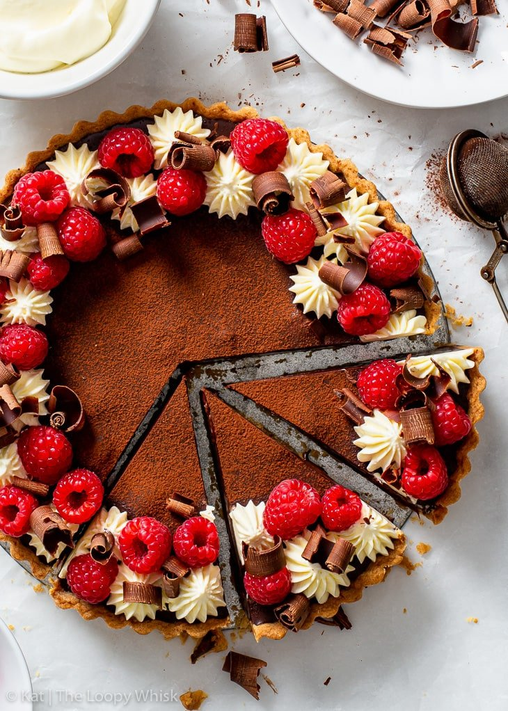 Overhead view of the vegan chocolate & raspberry tart, with a few slices already cut, on a sheet of white parchment paper.