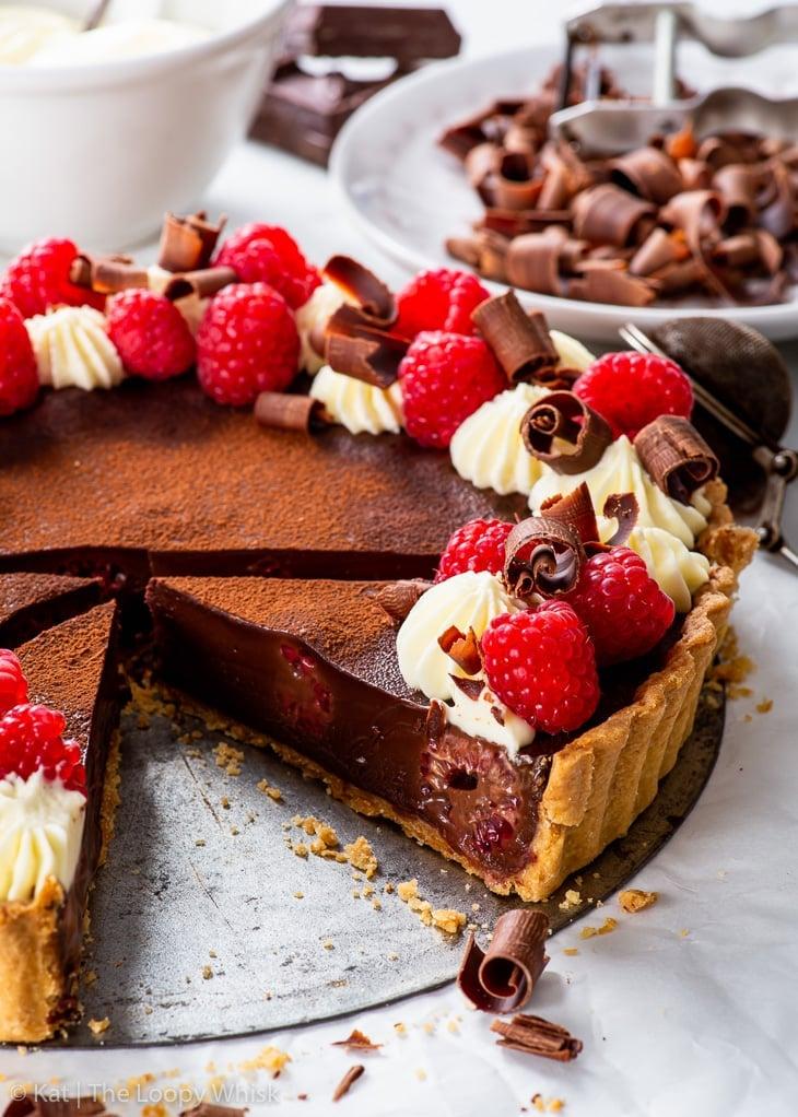 Vegan chocolate & raspberry tart, with a few slices already cut.