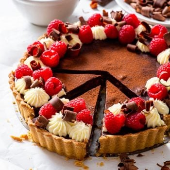 Vegan chocolate & raspberry tart, cut into individual slices, on a sheet of white parchment paper.