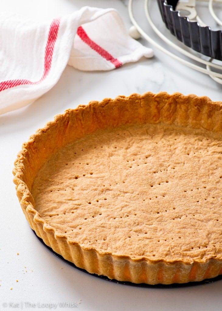 Blind baked vegan shortcrust pastry on a white surface.
