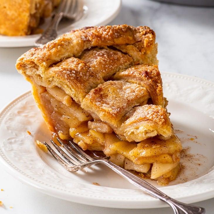 A slice of vegan apple pie on a white dessert plate.
