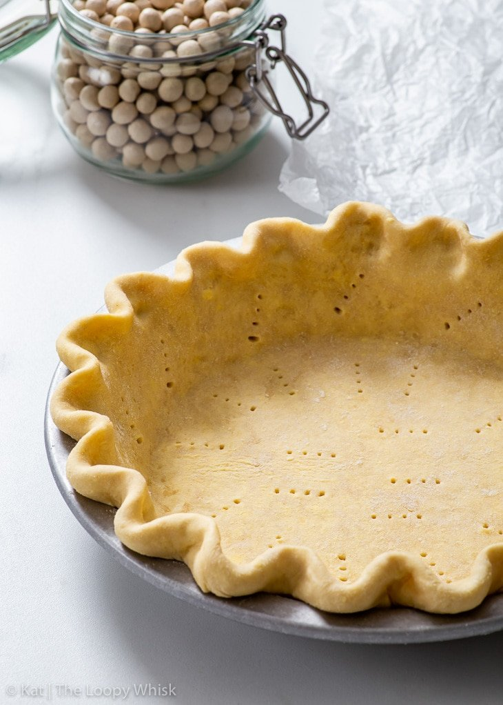 Vegan pie crust before baking, with a jar of pie weights in the background.