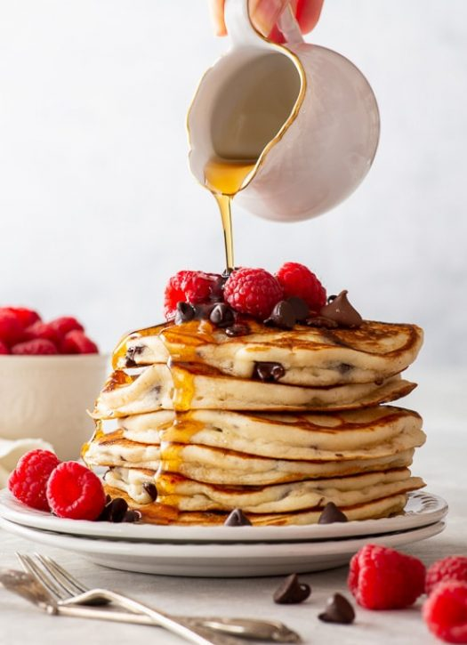 A tall stack of chocolate chip pancakes, topped with extra chocolate chips and raspberries. Maple syrup is being poured over the pancakes.