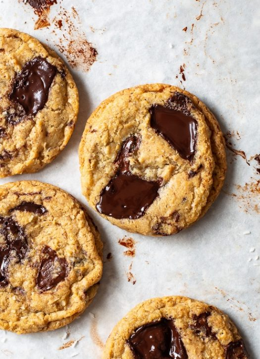 Coconut chocolate chip cookies on white parchment paper. The melted chocolate forms glossy pools on top of the cookies.