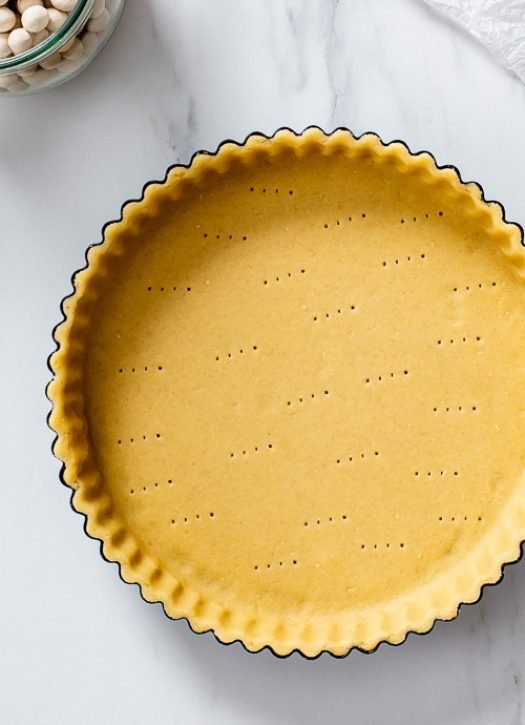 Overhead view of vegan shortcrust pastry crust that has been docked evenly with a fork.